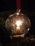 Kerze hinter einer Weihnachtskugel
